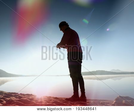 Leakage Of Light In The Lens. Tall Slim  Man Exercise   On The Mountain Lake Beach.