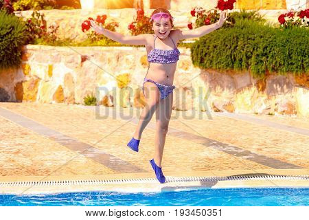 Joyful girl jumping to the pool, cute little child wearing goggles and flippers for diving, happy carefree childhood, enjoying summer holidays on the beach resort