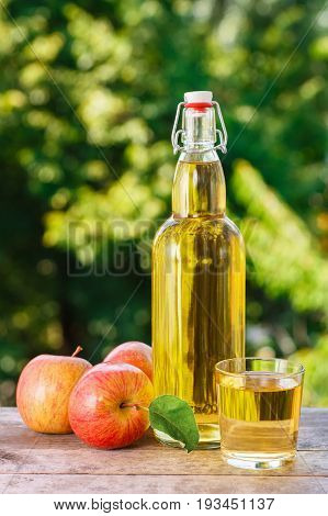 apple cider or juice in glass and in bottle with fresh apples on wooden table with blurred natural background. Summer drink