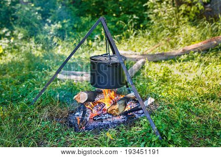 Cooking food at the stake outdoors. Camping, picnic in nature, camp food, hiking trip and tourism concept. Saucepan at the stake. Campfire. Kettle on fire