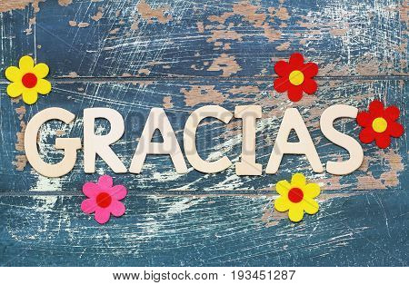 Gracias (which means thank you in Spanish) written with wooden letters on rustic surface and colorful flowers