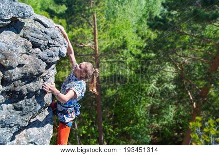 Teenager rock climber climbs on a rocky wall. Rock climber girl. Willpower success concept.