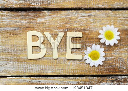 Bye written with wooden letters and white daisy flowers