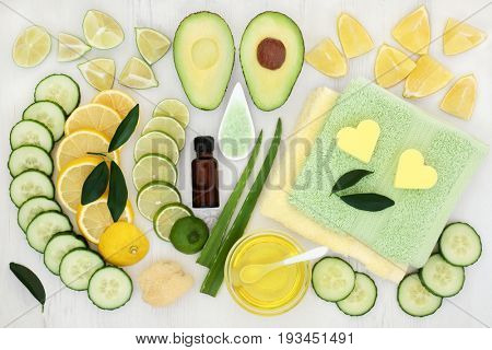 Body and skin care aromatherapy beauty treatment with cucumber, avocado, aloe vera and citrus fruit with essential oil, exfoliating salt and flannels on distressed white wood background.