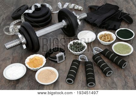 Weight training equipment for body builders with dumbbell weights, hand grippers, dietary food powder supplements, vitamin pills, heart rate monitor watch, leather gloves and tape measure.