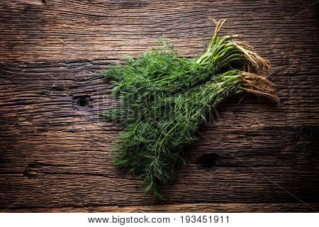 Dill.Bunch of dill on very old rustic oak table.