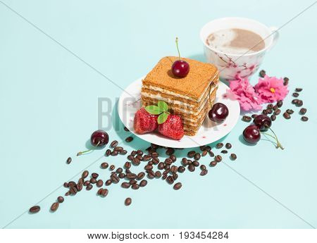 Tasty piece of cake on the white plate and cup of coffee, decorated with flowers, coffee beans, strawberries and cherry on the light mint background with empty place, perspective view, diagonal composition