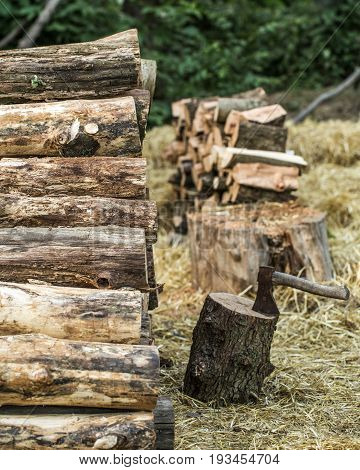 A deck of stacked logs and an axe in a log, the concept of drilling wood