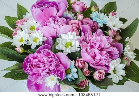Bright beautiful bouquet of flowers with white chrysanthemums pink peony with green leaves for birthday for holiday