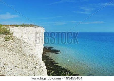 Aerial View To Blue Turquoise Water Of English Channel And A Little White Sailboat At The Background
