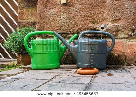 Two plastic watering cans green and gray ready for pour the garden standing on the stone pavement near the wall Heidelberg Germany.