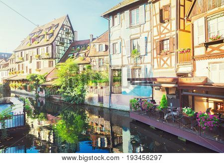 half timbered crooked houses of Colmar with reflections, Alsace, France, retro toned
