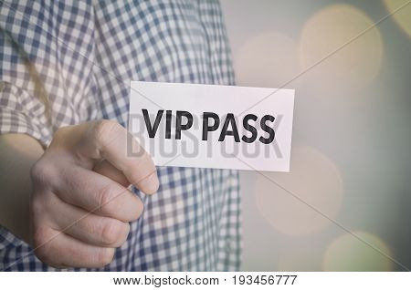Vip pass in hand with bokeh lights background