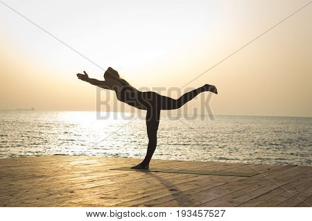 silhouette of young woman do yoga exercices outdoor, morning training in the sea