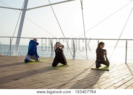 group of young people practicing in an outdoor yoga class. morning yoga exercices on wooden pier, sea background
