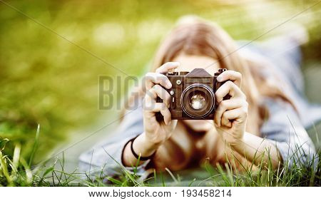 girl photographer makes a photo lying in the grass