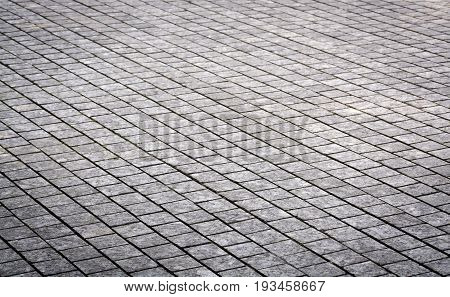 Stone pavement texture. Granite cobblestoned pavement background in diagonal perspective