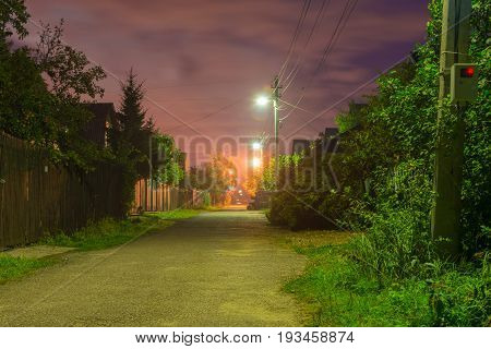 Village street at night in the light of street lamps