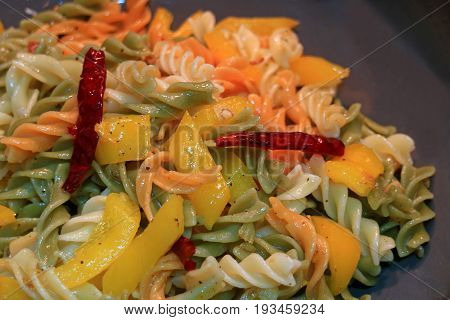 Fusilli pasta with garlic, dried red chili, yellow pepper and olive oil being cooked in a pan