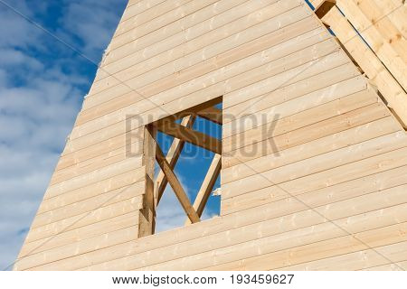 The window opening in the wall of a new wooden house under construction