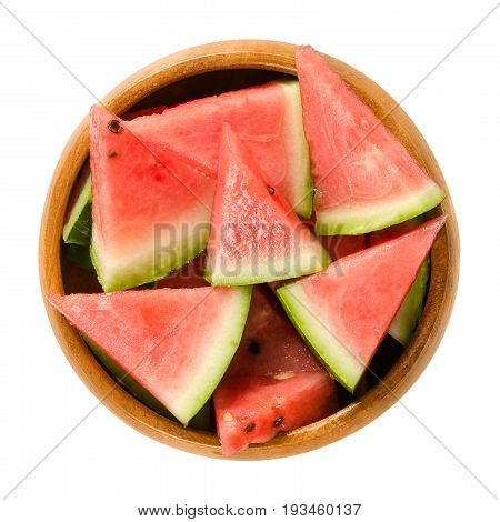 Watermelon slices in wooden bowl. Triangular pieces of raw Citrullus lanatus. Edible fruit with green hard rind, black seeds and red, sweet, juicy flesh. Macro food photo closeup from above over white