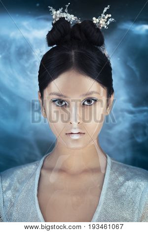 Portrait of futuristic young woman. Beautiful young multi-racial Asian Caucasian model girl in silver urban clothes with conceptual hairstyle and make-up against space background looking at camera. Sci-fi poster style.