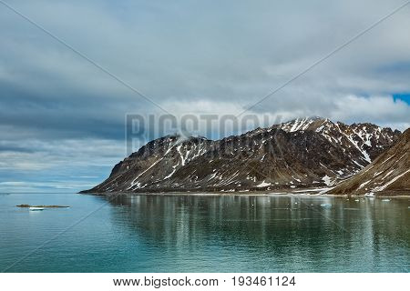 Cloudy sky and mountains along the Magdalenafjord in Svalbard islands Norway