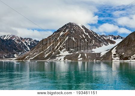Clouds and mountains along the Magdalenafjord in Svalbard islands Norway