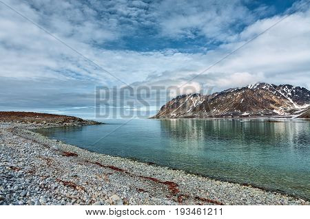 Cloudy sky and mountains along the bank in Magdalenafjord in Svalbard islands Norway