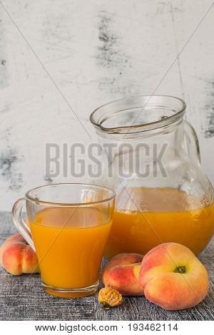 Freshly prepared natural peach juice with pulp in a glass jug and in a mug, next to ripe peaches on a dark wooden table. The concept of healthy eating.