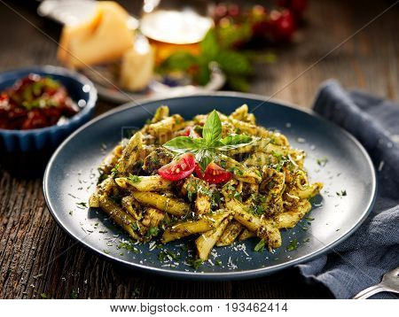 Penne pasta with spinach and chicken, sprinkled with parmesan cheese and fresh parsley