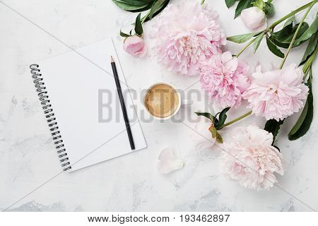Morning coffee mug for breakfast empty notebook pencil and pink peony flowers on white stone table top view in flat lay style. Woman working desk.