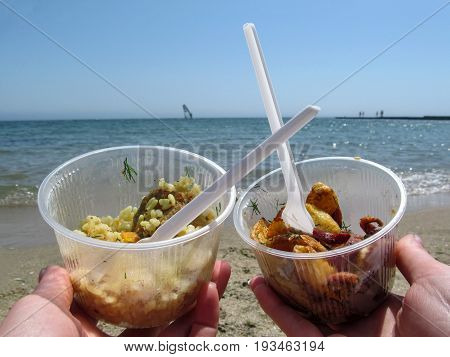 Two disposable plastic tableware with delicious takeaway food on the beach. Pilaf and potatoes with sausage in plastic containers on the sea background