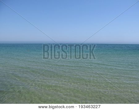 Calm clear sea and horizon hidden behind the haze. Sea blue background