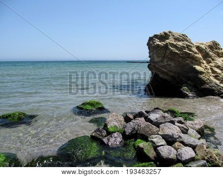 Many green stones in the foreground and one rock on the right are in turquoise sea water against a clear blue sky. Beautiful seascape on a clear sunny day