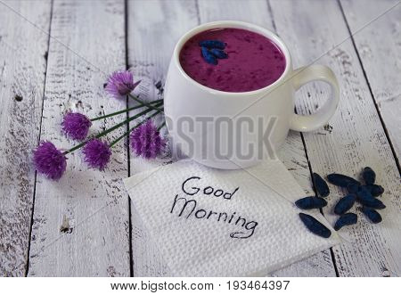 Cup of honey berry smoothie with summer flowers and good morning text on white napkin. Morning still life with healthy breakfast. Beautiful summer vintage background, vegetarian and vegan concept