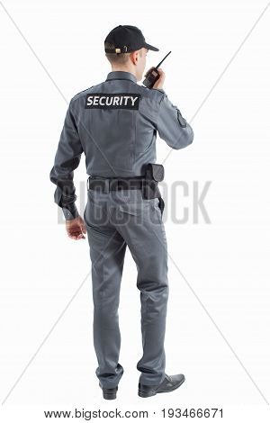 Security man on white stands with his back and speaks by walkie-talkie