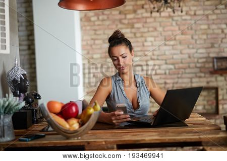 Sexy young woman using laptop computer and mobilephone  at home.