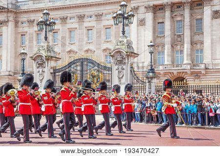 LONDON, UNITED KINGDOM - JULY 11, 2012: The band of the Grenadier Guards, led by a Drum Major of the Coldstream Guards, marches past the front of Buckingham Palace during the Changing of the Guard ceremony.