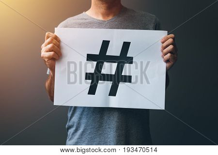 Hashtag as viral web social media network concept for marketing trending blogging and internet themes. Man holding paper with hash tag symbol.