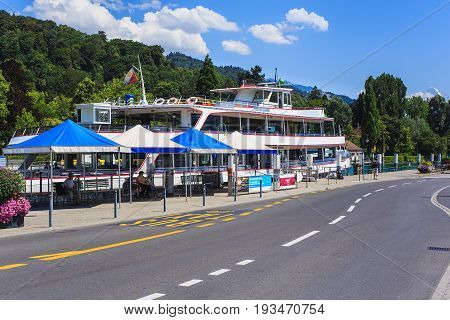 Thun, Switzerland - 21 July, 2015: road and pier in the city of Thun, mountains in the background. Thun is a city and municipality in the administrative district of Thun in the Swiss canton of Bern, located where the Aare river flows out of Lake Thun