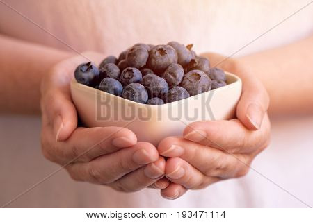 Woman offering a bowl of blueberries or bilberries selective focus
