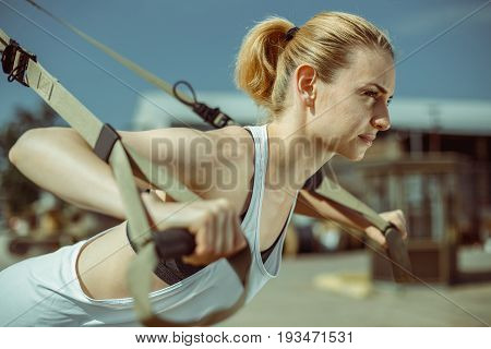 Portrait of young attractive woman does suspension training with fitness straps outdoors in urban city.