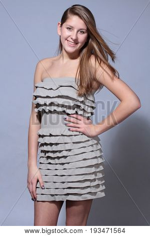 Beauty shot of a smiling long haired young beautiful young woman with her hair fluttering on the wind.