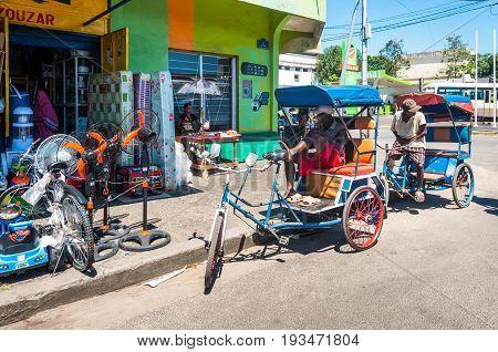 Toamasina Madagascar - December 22 2017: Malagasy rickshaws driver resting in his typical rickshaw padicab traditional transportation in Toamasina (Tamatave) Madagascar East Africa.