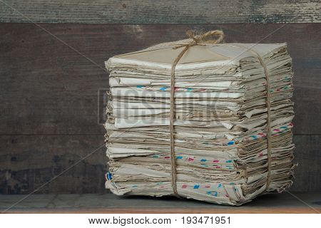 A pile of old letters tied with a rope lies on a wooden table