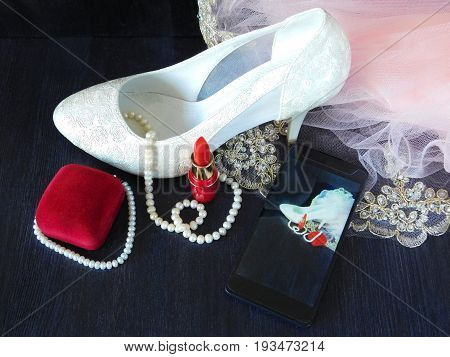 White women's shoes with high heels, red lipstick, present box and smartphone with the photo in the screen