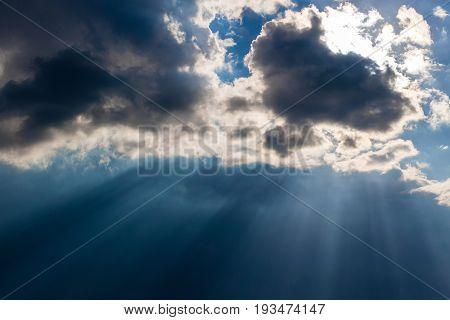 Heavy leaden sky with breaking sun rays