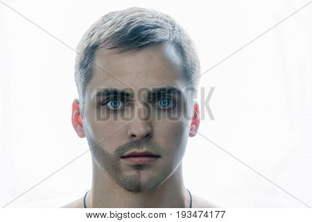 Portrait of man with half shaved beard. Skin care and hygiene. A guy with blue eyes is standing on a white background.