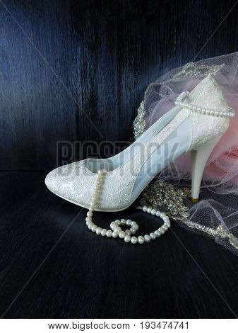 White stylish high heel shoe and pearl jewellery for a special occasion on a dark background. Empty place for a text